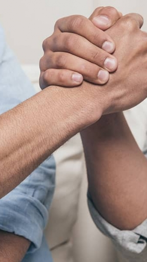 Clasped hands illustrate the connection between men at this event.
