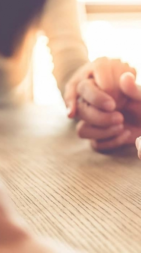 Women praying with linked hands illustrates the concept of Bible study and prayer.